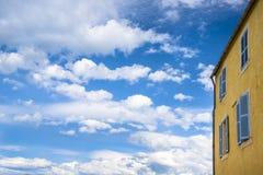 Gelbes Haus mit blauen Fenstern. Lizenzfreie Stockfotografie