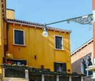 Gelbes Haus mit Blumen und Bank Bunte Häuser in Burano-Insel nahe Venedig, Italien Venedig-Postkarte Berühmter Platz Lizenzfreie Stockfotos
