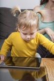 Gelbes Hemd des Babys, das Tablette betrachtet Lizenzfreies Stockbild