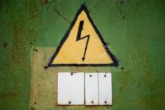 Gelbes Hochspannungszeichen auf gealterter grüner Wand Stockfotografie