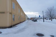 Gelbes Holzhaus auf einer schneebedeckten Straße in Kristinehamn Varmland S Stockfotografie