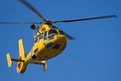Gelbes Hubschrauberflugwesen im blauen Himmel Lizenzfreies Stockfoto