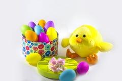 Gelbes Küken mit einer Geschenkbox mit bunten Eiern Ostern Lizenzfreie Stockfotos