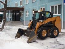 Gelbes kleines, die Straßen von großen Mengen Schnee in der Stadt nach Schneefällen säubernd Ein Schneepflug, der eine Straße klä stockbilder