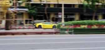 Gelbes Lamborghini Gallardo, das sehr schnelles auf der Straße fährt Springen, um einen Frisbee, unscharfen Hintergrund abzufange lizenzfreies stockfoto