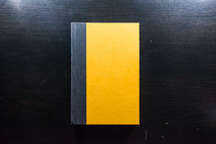 Gelbes leeres Papier des festen Einbands Front Book Pages Black Desk stockfotos