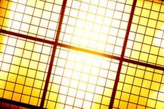Gelbes Licht mit einem Eisengitter in der Front Stockfotografie
