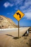 Gelbes Linkskurvezeichen entlang der Wicklung Pazifikküste-Landstraße Stockbild