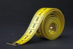 Gelbes Maßband auf schwarzem Hintergrund Stockfotografie