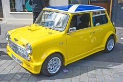 Gelbes Mini Cooper mit schottischer Markierungsfahne auf Dach Stockbilder