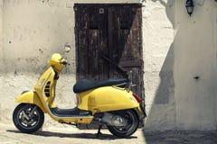 Gelbes Motorrad des Rollers vor alten Häusern mit weißer Wand Lizenzfreies Stockfoto