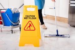 Gelbes nasses Vorsicht-Zeichen auf nassem Boden in der Küche Stockfotografie