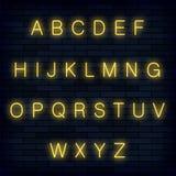 Gelbes Neonalphabet auf blauem Ziegelstein-Hintergrund Retro- Buchstaben Realictic-Art Satz Grafische Schriftart Lizenzfreie Stockfotografie
