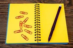 Gelbes Notizbuch und Feder Lizenzfreie Stockbilder