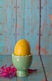 Gelbes Osterei in einem grünen Ei-Pastellhalter lizenzfreies stockfoto
