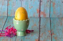 Gelbes Osterei in einem grünen Ei-Pastellhalter stockbild