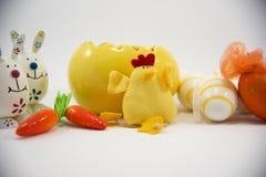 Gelbes Osterei und Huhn mit kleinen dekorativen Eiern und Karotten und Häschen 2. lizenzfreies stockfoto
