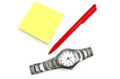 Gelbes Papier mit einer roten Feder, Armbanduhr Stockfotos
