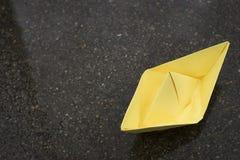 Gelbes Papierboot auf nass Asphalt, Stimmungskonzept, Kopienraum stockfoto
