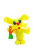 Gelbes Plasticinekaninchen mit Karotte Stockfotografie
