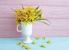 Gelbes schönes Blumenfrühjahr feiern das rustikale Blühen in einem Vase auf einem farbigen hölzernen Hintergrund Stockfotos