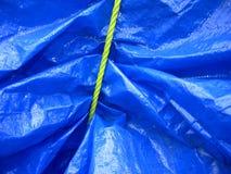 Gelbes Seil auf blauer Plane Stockfoto