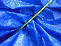 Gelbes Seil auf blauer Plane Stockfotografie