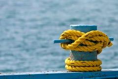 Gelbes Seil auf Schiffspoller Stockfotos
