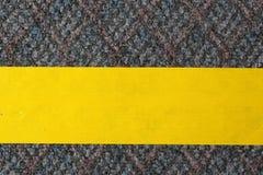 Gelbes selbsthaftendes Kreppband auf dem Teppich Lizenzfreies Stockbild