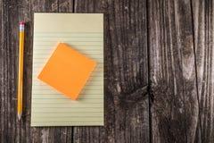 Gelbes Tablet auf Weinlese-Schreibtisch Stockfotos