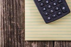 Gelbes Tablet u. Taschenrechner auf Weinlese-Schreibtisch Stockfoto