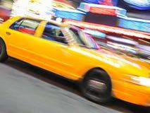 Gelbes Taxi, das nahe Times Square in New York beschleunigt. Lizenzfreie Stockfotos