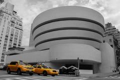 Gelbes Taxi im Hintergrund des Guggenheim in New York Stockfoto