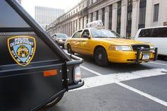 Gelbes Taxi und Nypd-Fahrzeug in Manhattan Stockfoto