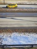 Gelbes Taxiauto auf umfaßtem Boden des Straßenlichtschnees lizenzfreie stockbilder