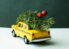 Gelbes Taxiauto mit einem Baum auf dem Stamm auf einem grünen Retro- Hintergrund Stockfoto