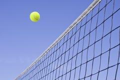 Gelbes Tennis-Kugel-Flugwesen über dem Netz Lizenzfreies Stockbild