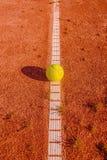 Gelbes tennisball auf einem alten Gericht Stockfotografie