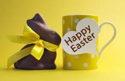 Gelbes Thema glückliche Ostern-Tupfenfrühstücks-Kaffeetasse mit Schokoladen-Häschen Lizenzfreie Stockfotografie