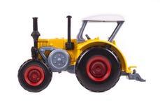 Gelbes Traktorspielzeug auf weißem Hintergrund Lizenzfreies Stockfoto
