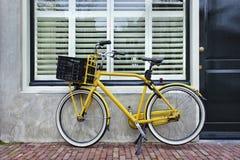 Gelbes Transportfahrrad parkte gegen erneuertes Haus, Amsterdam, die Niederlande Lizenzfreie Stockfotos