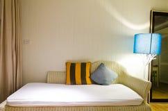 Gelbes und braunes Kissen auf Sofa Stockfotografie