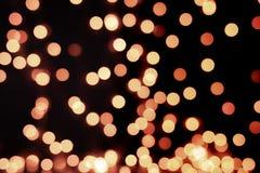Gelbes und orange Weihnachtsbaum bokeh auf schwarzem Hintergrund von defocused funkelnden Lichtern, Weihnachtshintergrund-Musterk lizenzfreie stockfotografie