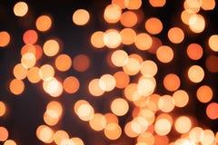 Gelbes und orange Weihnachtsbaum bokeh auf schwarzem Hintergrund von defocused funkelnden Lichtern, Weihnachtshintergrund-Musterk stockbilder