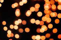 Gelbes und orange Weihnachtsbaum bokeh auf schwarzem Hintergrund von defocused funkelnden Lichtern, Weihnachtshintergrund-Musterk stockfoto