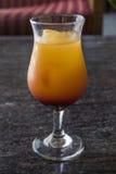 Gelbes und rotes tropisches Cocktail mit einem Eiswürfel an einem heißen Sommertag Stockfoto