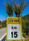 Gelbes und weißes Kilometer-Anzeichen singen verziert mit zwei Büschen stockfotos