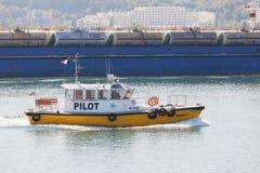 Gelbes und weißes kleines Versuchsboot kommt den Hafen Stockfotos