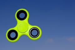 Gelbes Unruhe SPINNER-Druckentlastungsspielzeug auf Himmelhintergrund Stockfoto