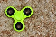 Gelbes Unruhe SPINNER-Druckentlastungsspielzeug auf Steinhintergrund Stockbilder